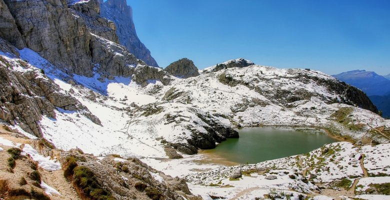 lago di coldai surrounded by snow