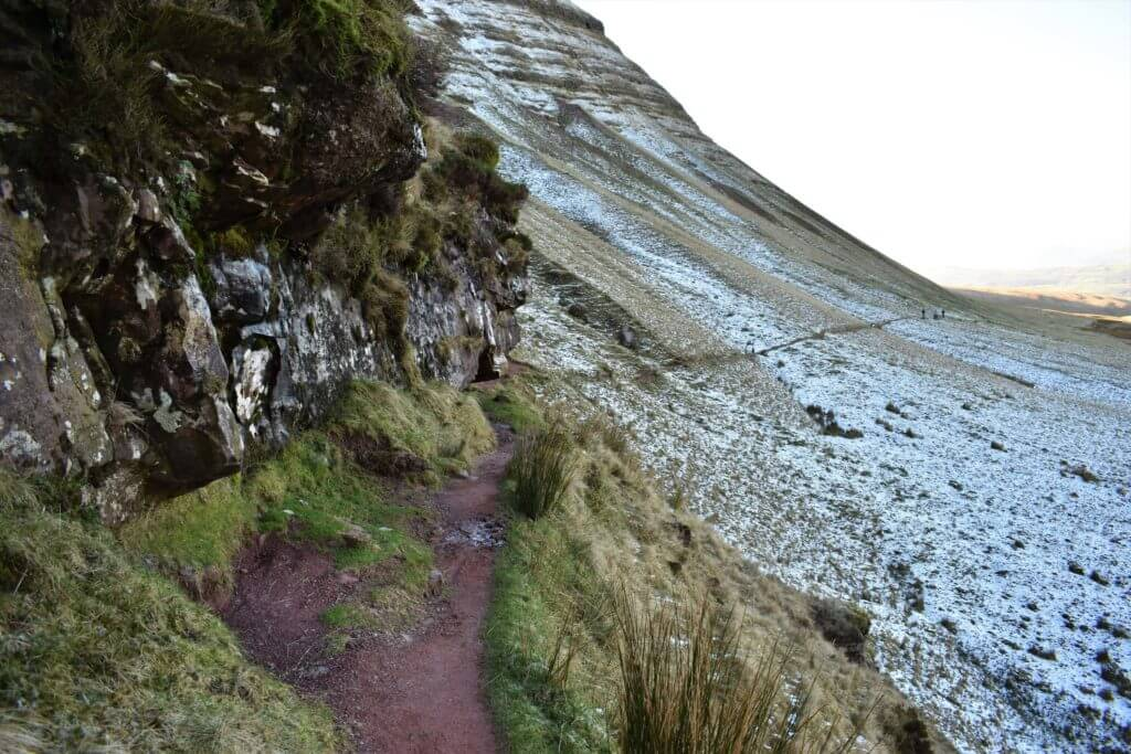 trail leads under the cliff below picws du