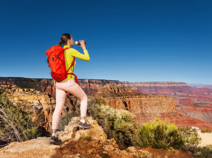 female hiker drinking water at the grand canyon